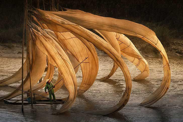Китайски рибар се труди, докато вятърът опъва мрежите му