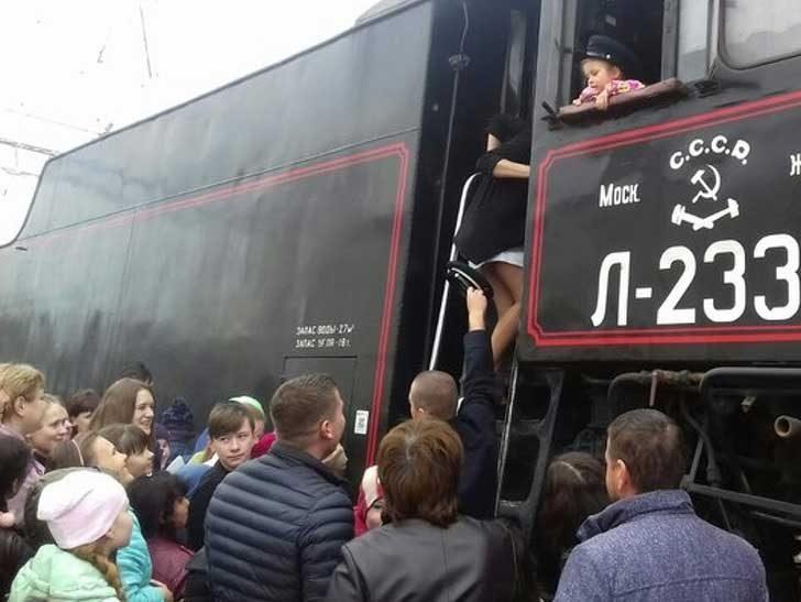 Служител на железниците, който помага на младо момиче да запази благоприличие