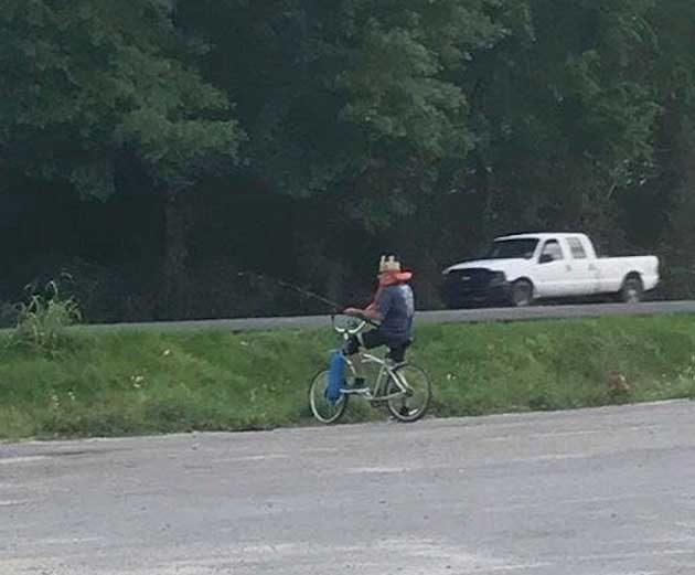 """""""Този приятел лови риба в празната канавка на натоварена магистрала, носейки спасителна жилетка и шапка от Burger King, седейки върху колелото си"""""""