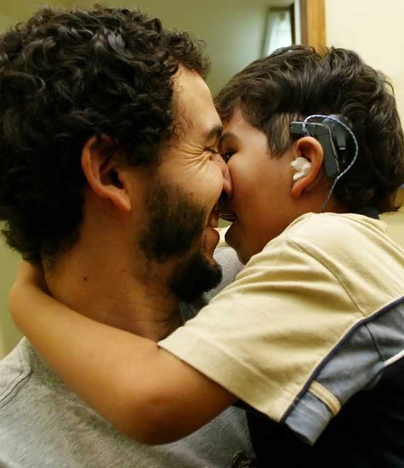 Един щастлив баща, държащ сина си, който е чул за пръв път неговия глас