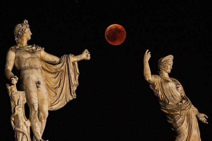 Снимка на две антични статуи и кървава луна за фон