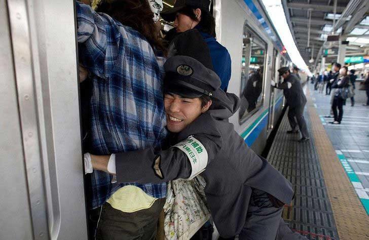 Специални служители, които натъпкват хората във влаковете в Токио, Япония